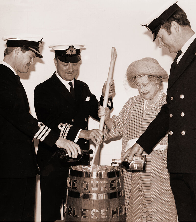 Great Britain's Queen Mother assists with the stirring of the Royal Navy's traditional Pusser's Rum Fleet Christmas Cake